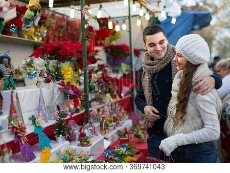 Smiling Parents At Counter Of X-mas Market. Shallow Depth Of Focus Only On Man