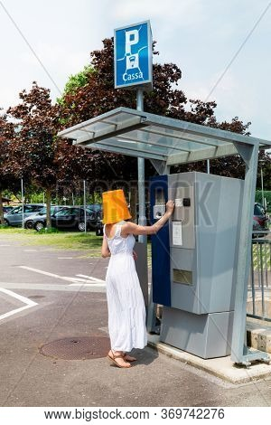 A woman pays the car park with a bucket on her head, Very funny concept.
