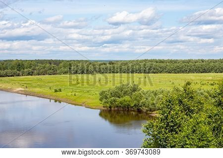 A Small River Flows Around The Forest, With The Reflection Of The Trees In It Against The Blue Sky.