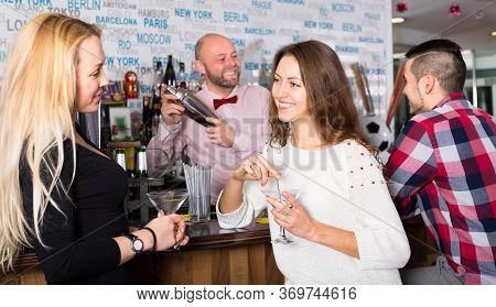 Two Women And A Man At The Bar. Women Are Talking And A Man Is Waiting For His Drink While The Barte