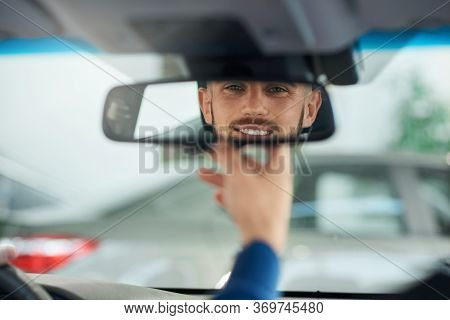 Back View Of Young Handsome Man Looking And Holding Small Rear View Mirror While Driving Car. Close