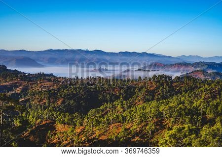 A Beautiful And Soothing Landscape Of Mountains Covered In Clouds And Green Trees During Winters.
