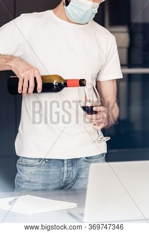 Cropped View Of Man In Medical Mask Pouring Wine In Glass Near Laptop On Worktop