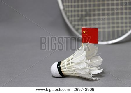 Mini China Flag Stick On The White Shuttlecock On The Grey Background And Out Focus Badminton Racket