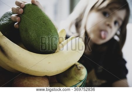 Little Girl Hand Taking An Avocado From A Fruit Basket - Child\'s Hand Holding Fresh Green Ripe Avoc