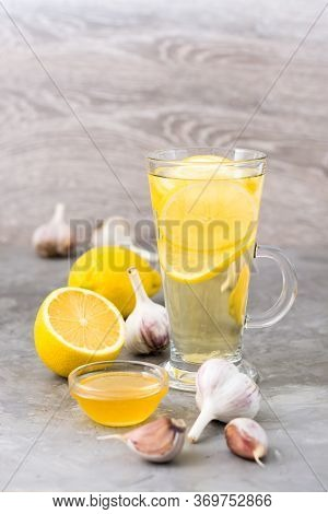 Therapeutic Drink Of Lemon, Honey And Garlic In A Glass On The Table. Alternative Medicine
