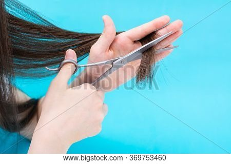 Children's Hand Cuts The Ends Of The Hair On A Blue Background. Quarantine Yourself