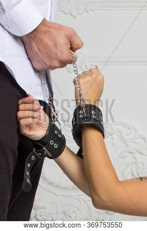 The Concept Of Domestic Violence. Feminine Hands In Handcuffs. Handcuffs Are Held By A Man.