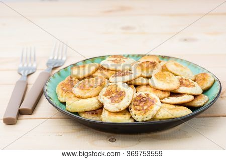Trend Breakfast. Dutch Mini Pancakes On Plate And Two Forks On A Wooden Table.