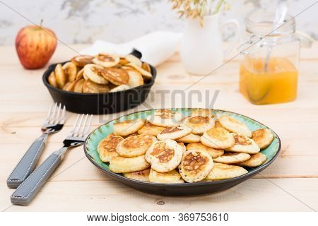 Trend Breakfast. Dutch Mini Pancakes On A Plate And A Frying Pan With Them On A Wooden Table.
