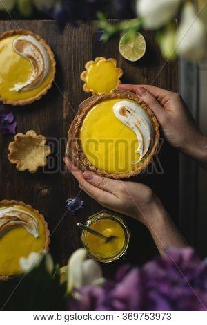 Female Hands Holding Lemon Meringue Tart On Dark Rustic Table
