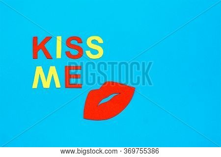 World Kiss Day. Red Lips And The Inscription Kiss Me From Colored Cardboard On A Blue Background.