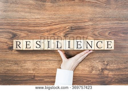 Resilience Word On Wooden Building Blocks With Supporting Hand. Recovering And Building Resilience C