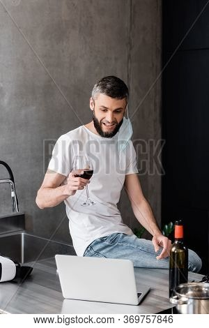Smiling Man In Medical Mask Holding Glass Of Wine Near Laptop And Vr Headset On Worktop In Kitchen