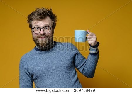 Attractive Man With A Shaggy Hairstyle, Glasses And An Old Sweater With A Mug Of Hot Drink Has A Goo