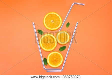 Creative Flat Lay Composition Made Of Orange Slices, Fresh Mint Leaves And Cocktail Straws On A Brig