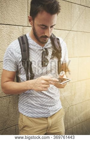 Cheerful Man Wanderer Use Cell Telephone While Standing Against Street Wall With Copy Space Area