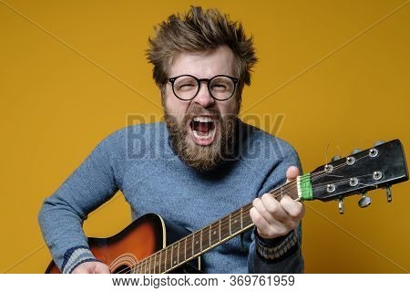 Funny Hipster In An Old Sweater Plays An Acoustic Guitar And Sings Loudly, On A Yellow Background. H