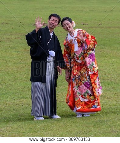 Cute Japanese Couple In Colorful Traditional Clothing In Nara Park, Japan