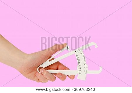 Female Hand Holding Caliper On Pink Background. Copy Space. Weight Loss And Slimming Treatment Conce
