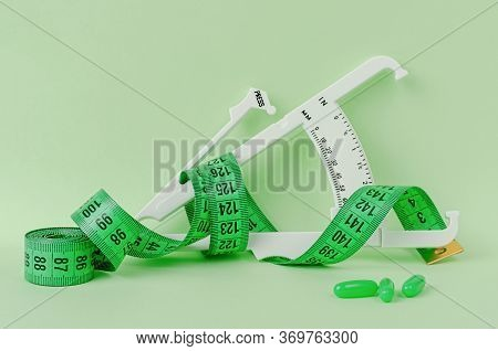 Slimming Treatment Concept. Measuring Tape, Supplement And Caliper On Green Background.