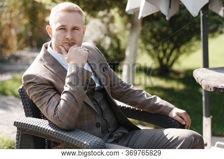 Thinking Man In Beige Checkered Jaket Sitting On The Chair Outside. Groom Portrait