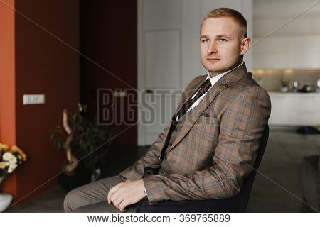 Serious Man In Beige Checkered Jaket Sitting On The Armchair. Groom Portrait