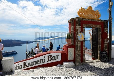 Fira, Greece - May 17: The View On Fira Town And Tourists Enjoying Their Vacation In A Bar On May 17