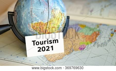 Travel Tourism 2021 Text On A White Sheet On Globe On The Blue Background Of The Atlas Map