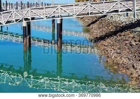 Water Reflections Of Walkway Down To Boats Moored At The Marina