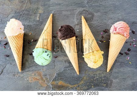 Ice Cream Cone Flat Lay Over A Dark Slate Background. Vanilla, Mint, Chocolate, Lemon And Strawberry