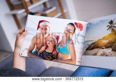 Woman Looking At Photo Album Or Photobook