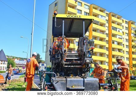 Hustopece, Czechia - May 18, 2020: Workers Make Blacktop. New Asphalt Is Laid Over The Old Asphalt A