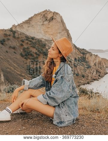 Beautiful Girl In A Hat On A Summer Vacation In The Mountains On Nature. Blue Sky And Sea.
