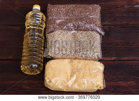 Sunflower Oil And Various Packages Of Cereals On A Brown Wooden Textured Background