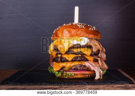Huge Burger With Beef, Bacon, Cheese, Fresh Vegetables And Sauces On Plate Over Wooden Background. F
