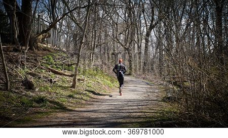 Solitary Male Runner Jogging Along A Gravel Pathway In A Lovely Wooded Area In The St. Catharines, O