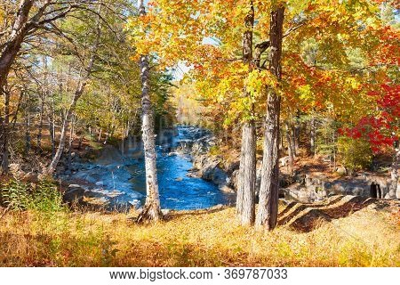 Coos Rapids And Stream Flow Through Autumnal Colored Forest, Maine, Usa.