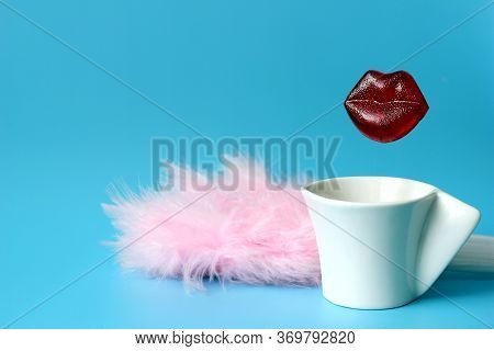 Delicious Caramel Lips Over A Coffee Cup Next To Pink Feathers On A Blue Background. The Concept Of