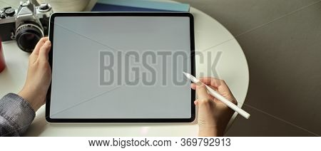 Female Freelancer Working With Digital Tablet With Stylus Pen On Coffee Table At Home