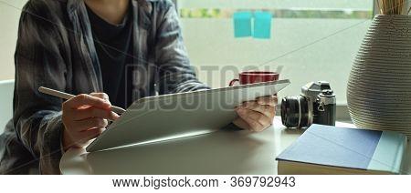 Female Freelancer Working On Digital Tablet With Stylus Pen On Coffee Table Beside Window