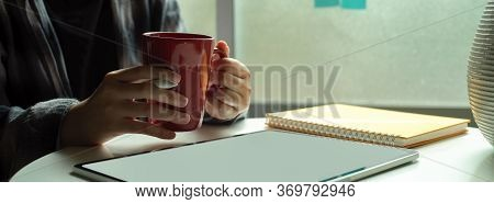 Female Freelancer  Holding A Cup While Looking On Mock-up Tablet On Coffee Table Beside Window