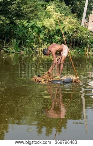 A Village Fisherman Is Throwing A Net For Fishing In A Pond