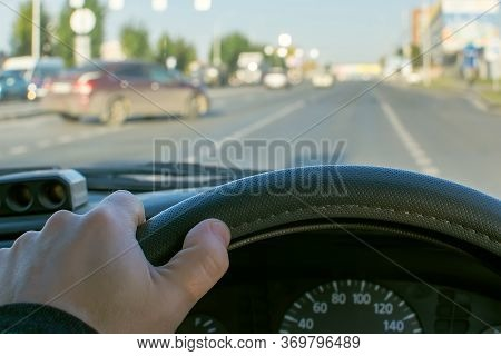 View Of The Driver Hand On The Steering Wheel Of A Car Against The Background Of A City Road And A C