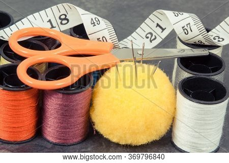 Spools Of Colorful Thread, Needle, Tape Measure And Scissors. Accessories For Sewing And Needlework
