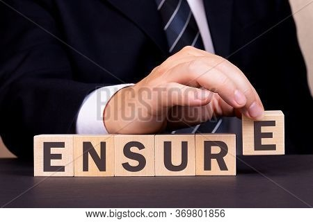Man Made Word Ensure With Wooden Blocks. Business Concept.