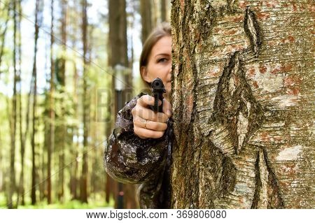 Military Woman Shoots With A Gun In Forest. Hunter Girl Hiding Behind A Tree With Weapons. Survival
