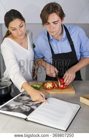 Handsome Young Man Cutting A Bell Pepper While A Beautiful Young Woman Hugs Him On An Out Of Focus B