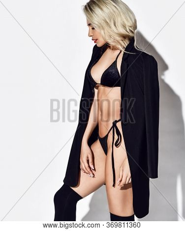 Sensual Slim Curly Blonde Woman In Sexy Black Bikini And Long Jacket Is Standing Side To Us And Look