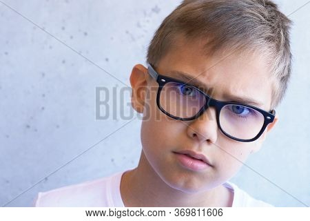 Smart Concerned Boy With Eye Blue Light Blocking Glasses Looking To Camera. Grunge Gray Wall Backgro